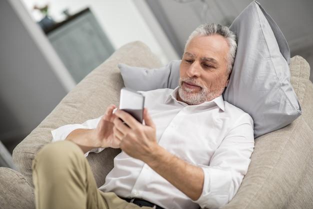 Temps de repos. heureux homme exprimant la positivité tout en regardant son téléphone et en lisant un message