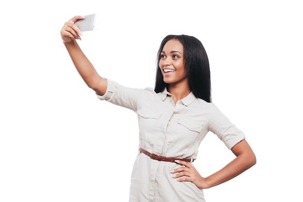 Temps de selfie. belle jeune femme africaine faisant selfie par son téléphone intelligent et souriant en se tenant debout sur fond blanc