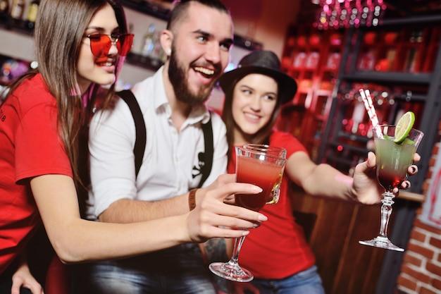 Temps selfie. un groupe d'amis lors d'une soirée dans une discothèque trinque avec des boissons alcoolisées. jeunes heureux avec des cocktails au pub.