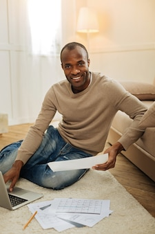 Temps de travailler. souriant homme afro-américain barbu aux yeux sombres souriant et travaillant sur l'ordinateur portable et tenant une feuille de papier assis sur le sol et d'autres papiers se trouvant près de lui