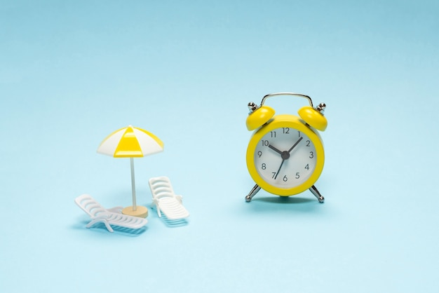 Le temps de voyager. chaise longue, parasol et réveil sur fond bleu.