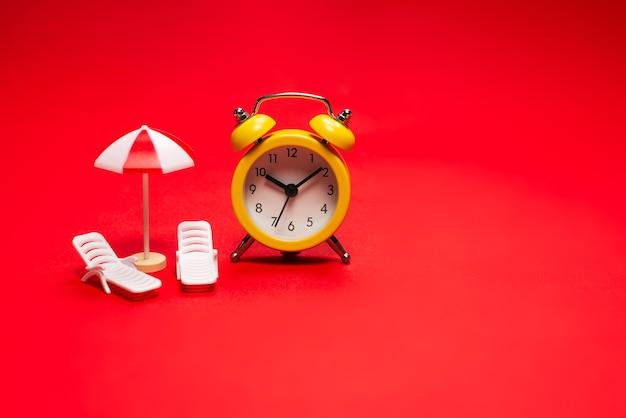 Le temps de voyager. chaise longue, parasol et réveil sur fond rouge.
