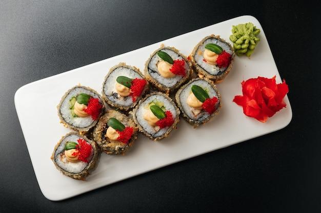 Tempura maki sushi rouleau de sushi frit fait de crevettes à l'avocat et fromage à la crème à l'intérieur du rouleau de sushi servi sur plaque blanche sushi japonais