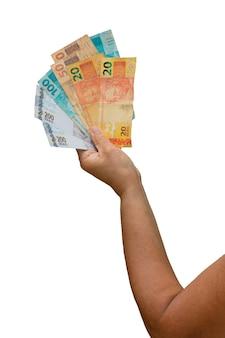 Tenant de l'argent réel brésilien, factures de 200, 100, 50 et 20 isolés sur un mur blanc. espace pour le texte.