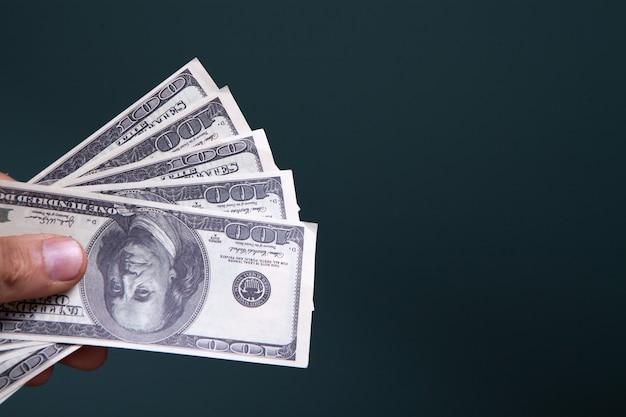 Tenant des billets d'un dollar sur un fond bleu