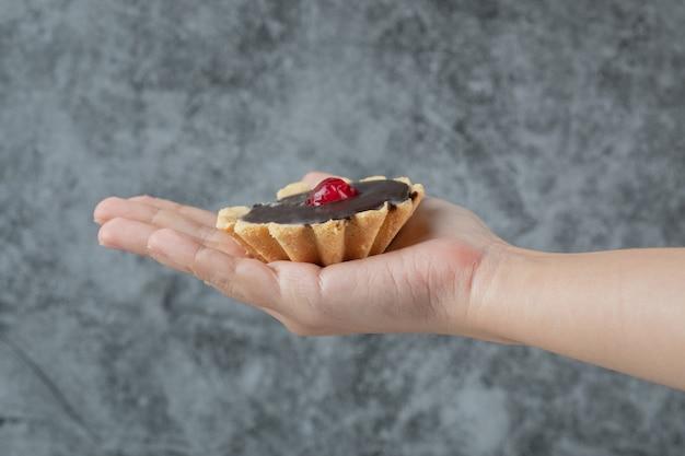 Tenant des biscuits au beurre croustillants dans la main.