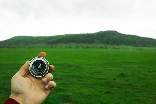 Tenant une boussole contre la scène d'un champ vert pendant la journée