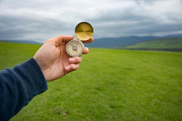 Tenant une boussole sur la scène d'un champ vert