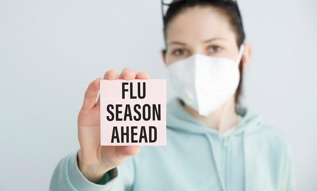 Tenant une carte avec le texte saison de la grippe, concept médical