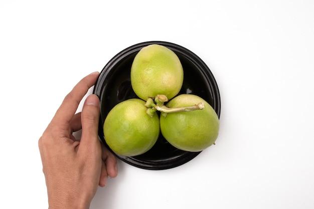 Tenant un citron sur une assiette sur fond blanc