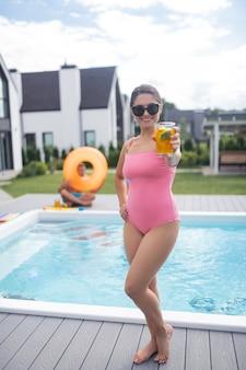 Tenant un cocktail d'été. belle femme portant un maillot de bain rose tenant un cocktail d'été