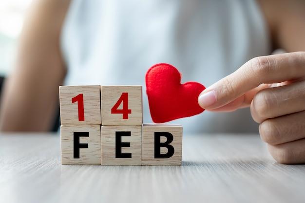 Tenant une décoration en forme de coeur rouge avec un cube en bois