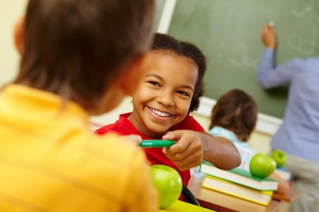 Tenant étudiant son crayon vert avec le professeur de fond