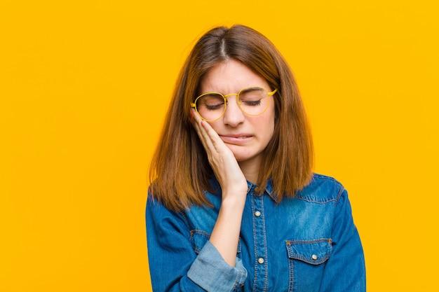 Tenant la joue et souffrant de maux de dents douloureux, se sentant malade, misérable et malheureux, à la recherche d'un dentiste