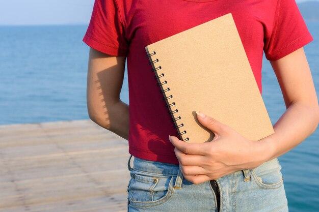 Tenant un livre marron