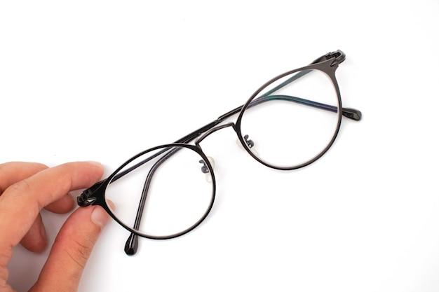 Tenant des lunettes sur un fond blanc
