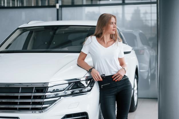Tenant des lunettes de soleil à la main. fille et voiture moderne dans le salon. le jour à l'intérieur. achat de véhicule neuf.