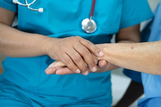 Tenant la main d'une patiente asiatique âgée avec amour