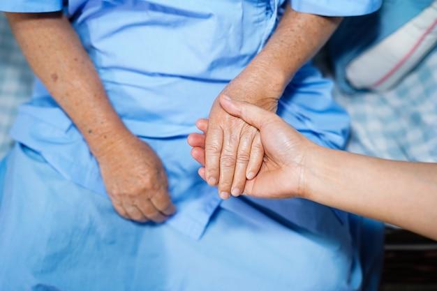 Tenant la main patiente senior asiatique avec amour et soin.