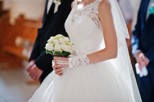 Tenant les mains du couple de mariage à l'église