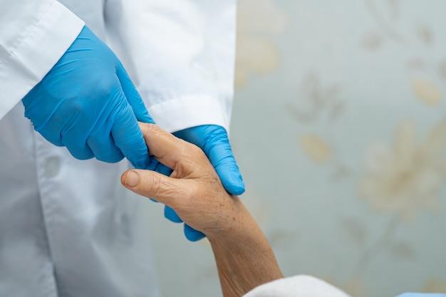 Tenant des mains touchantes, une vieille dame asiatique ou âgée, patiente avec amour, soins, aide, encouragement et empathie à l'hôpital de soins infirmiers : concept médical fort et sain