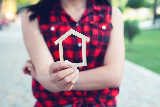 Tenant une maison à la main dans le parc