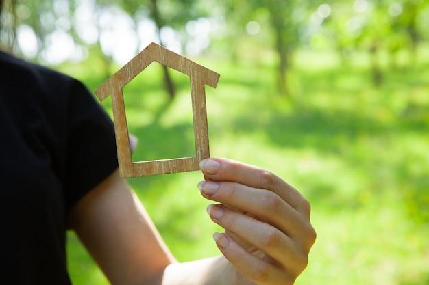 Tenant une maison à la main sur le fond de la nature