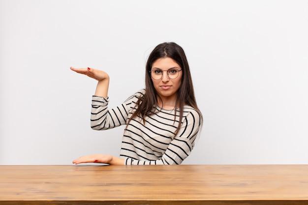 Tenant un objet avec les deux mains sur l'espace de copie latéral, montrant, offrant ou faisant la publicité d'un objet