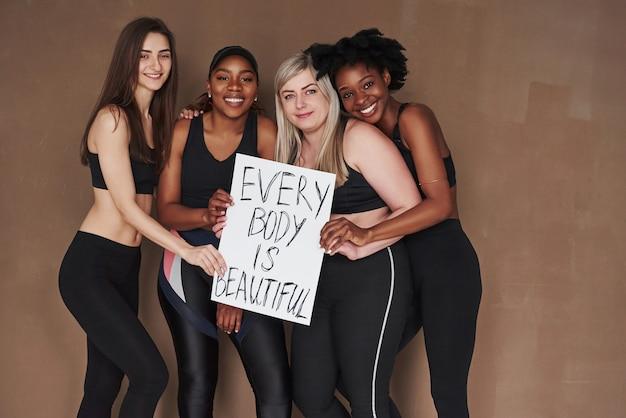 Tenant une pancarte avec des lettres de motivation. groupe de femmes multiethniques debout contre l'espace brun