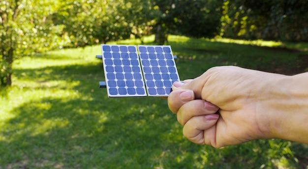 Tenant le panneau photovoltaïque d'énergie solaire