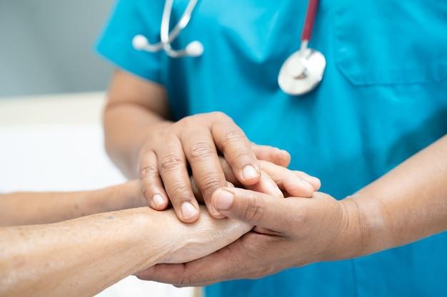 Tenant par la main une patiente asiatique âgée ou âgée avec amour, soins, encouragement et empathie dans la salle d'hôpital de soins infirmiers, concept médical solide et sain