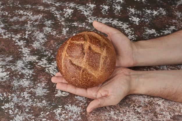 Tenant un petit pain dans la main.