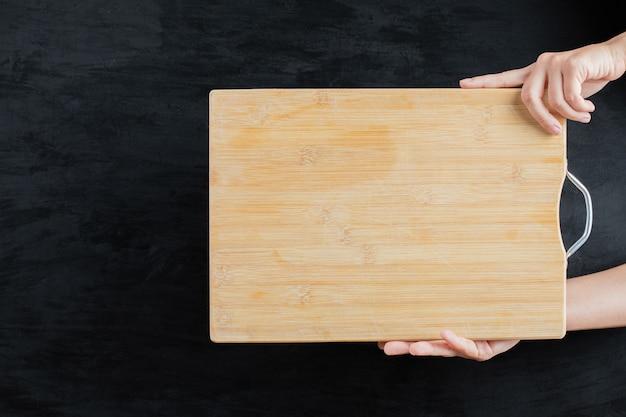 Tenant une planche de bois carrée sur fond noir