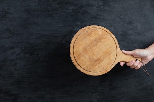 Tenant un plateau en bois à la main sur fond noir