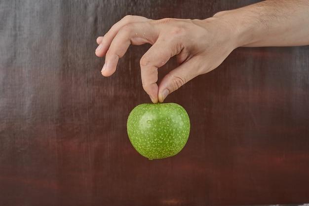 Tenant la pomme dans la main