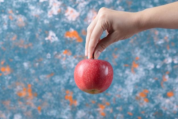 Tenant une pomme rouge de la tige sur fond bleu.