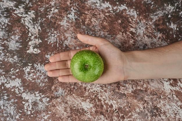 Tenant une pomme verte dans la main.