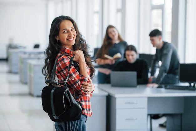 Tenant un sac noir. groupe de jeunes en vêtements décontractés travaillant dans le bureau moderne