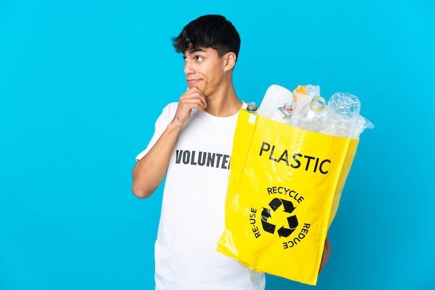 Tenant un sac plein de bouteilles en plastique à recycler sur bleu ayant des doutes et de la réflexion