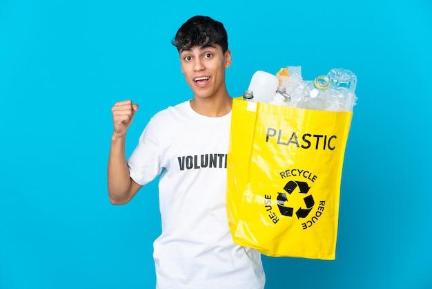 Tenant un sac plein de bouteilles en plastique à recycler sur bleu célébrant une victoire en position de vainqueur