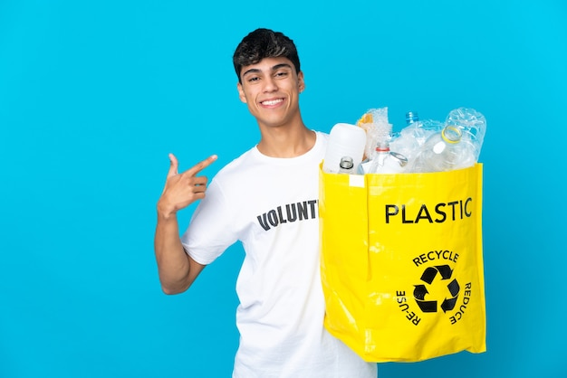 Tenant un sac plein de bouteilles en plastique à recycler sur bleu en donnant un geste de pouce en l'air