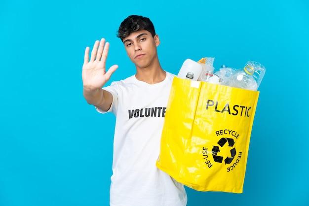 Tenant un sac plein de bouteilles en plastique à recycler sur bleu faisant le geste d'arrêt