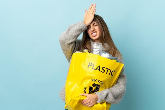 Tenant un sac plein de bouteilles en plastique à recycler sur bleu isolé ayant des doutes avec l'expression du visage confus
