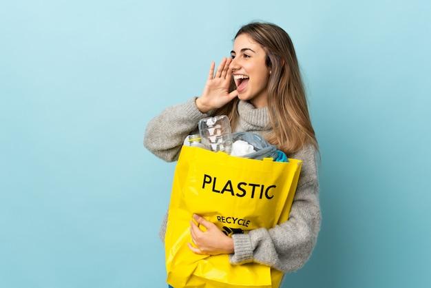 Tenant un sac plein de bouteilles en plastique à recycler sur des cris bleus avec la bouche grande ouverte