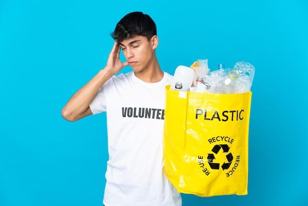 Tenant un sac plein de bouteilles en plastique à recycler sur fond bleu avec des maux de tête