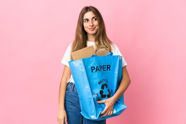 Tenant un sac de recyclage plein de papier à recycler sur rose isolé debout et regardant sur le côté