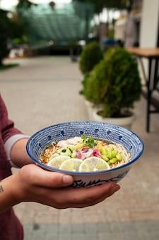 Tenant une soupe de nouilles ramen froide d'été avec du poulet