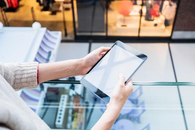 Tenant une tablette dans un magasin public. les mains des femmes tiennent un gadget dans un centre commercial