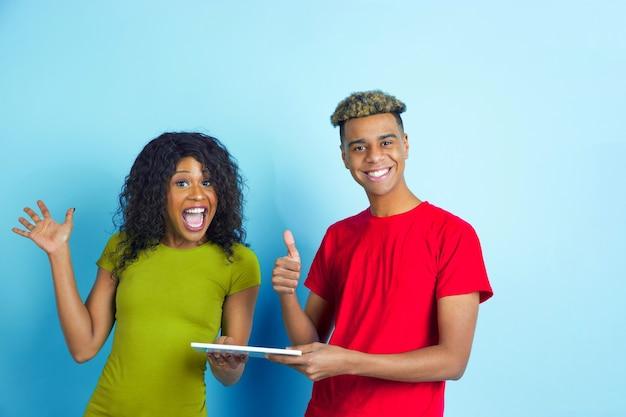 Tenant la tablette, les pouces vers le haut. jeune homme afro-américain émotionnel et femme dans des vêtements décontractés colorés sur fond bleu. beau couple. concept d'émotions humaines, expession faciale, relations, publicité.