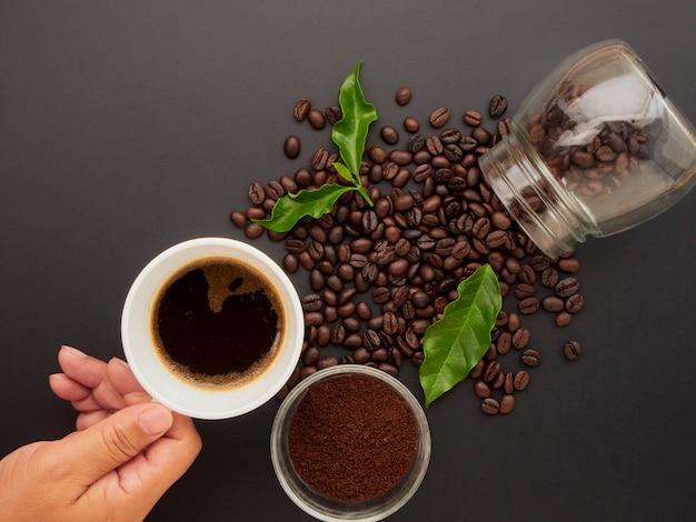 Tenant une tasse de café sur les grains de café.